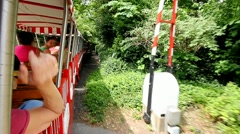 On board a mini train at a zoo while people waving as it passes them by - stock footage