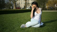 Woman eating an apple on the grass Stock Footage