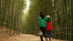Mother and daughter walking through Bamboo forest Stock Footage