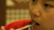 Beautiful little Asian girl eating food by chopsticks Stock Footage