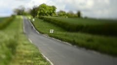 Cycling on a quiet country road (Tilt Lens) Stock Footage