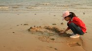 Stock Video Footage of Little Asian girl playing with sand on beach