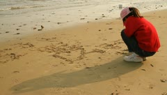 Little girl writing letters on sand of beach Stock Footage