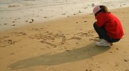 Stock Video Footage of Little girl writing letters on sand of beach