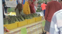 Stock Footage - Cusotmers check out asparagus at farmers market Stock Footage