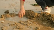 Hands of little girl playing with sand on beach Stock Footage