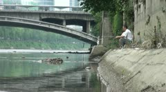 Fishing in a dirty river, pollution in Chinese city Stock Footage