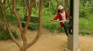 Stock Video Footage of Little Asian girl working out on exercise equipment at park