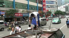 Men are taking fish out of a tank installed on a truck in China Stock Footage