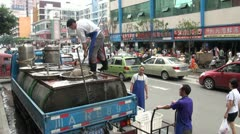 Scooping fish out of a tank in the middle of a road in Chengdu, China Stock Footage