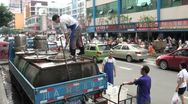 Stock Video Footage of Scooping fish out of a tank in the middle of a road in Chengdu, China