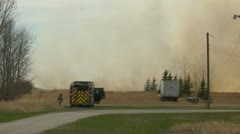 Grassfire, fire truck and crew RCMP car arrives, dramatic Stock Footage