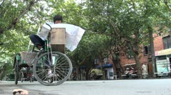 Worker at a tricycle is reading a map, seems lost in his own city, in China Stock Footage