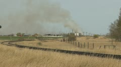grassfire, distant smoke along railway track - stock footage