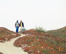 Young couple walking to beach on sandy path Stock Photos