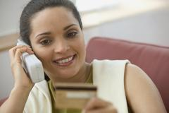 Woman ordering with credit card on telephone Stock Photos