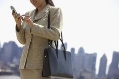 Businesswoman dialing cell phone with city behind her Stock Photos
