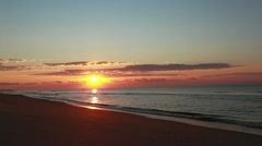 Beautiful beach sunrise with distant fishing boat Stock Footage