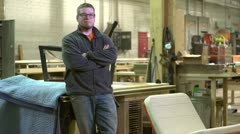 Proud owner of a woodworking business standing in his shop - stock footage