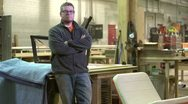 Proud owner of a woodworking business standing in his shop Stock Footage