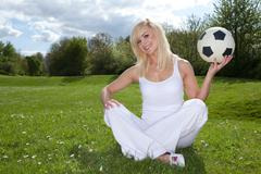 smiling woman about to throw a football - stock photo
