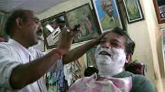 Inside a barber shop in India - shaving off the beard Stock Footage