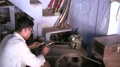 Indian worker shaving knives in a 'blue house' Stock Footage