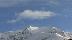 Clouds and Spindrift Pulsing over Snowy Crag Mountain Stock Footage