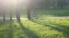 two cyclists riding down the road in the park - stock footage