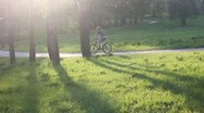Two cyclists riding down the road in the park Stock Footage