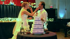 Bride and Groom Feeding Cake to Each Other at Reception - stock footage