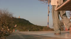 Pilgrims slowly walking towards a sacred peak in India Stock Footage