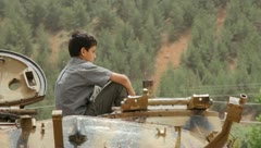Child sitting atop Iraqi tank (HD) c Stock Footage
