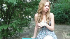 Women sadly sitting on bench and playing with her long blond hair Stock Footage