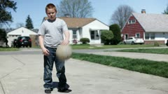 Boy practicing basketball in driveway Stock Footage