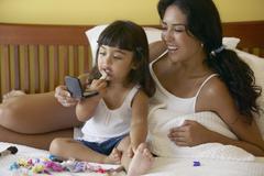 Mother and daughter applying makeup Stock Photos