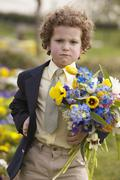Young boy with angry face holding flowers outdoors Stock Photos
