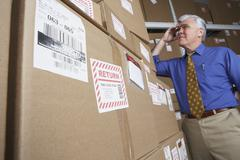 Businessman in warehouse looking at returned packages Stock Photos