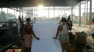 Newly dyed fabric being rolled garment factory, India Stock Footage