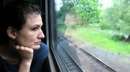 Woman sits in train near window during movement Stock Footage