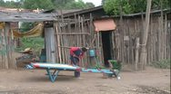 Stock Video Footage of African mechanic shop two men repairing a donkey cart, trucks pass by WS