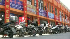 Motorbikes parked in front of a second hand market in Shanghai, China Stock Footage