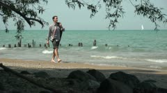 Business man walking happily on the beach - stock footage
