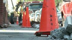 Dugup sidewalk with orange work cones and bulldozer city tree planting Stock Footage