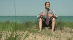 Business man loosening his tie on the beach - stock footage