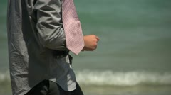Business man skipping stones in the ocean, close up - stock footage