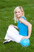 young blonde woman dressed in blue with a ball - stock photo
