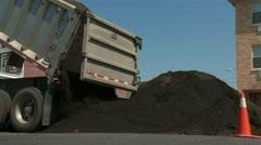 Truck dumps soil onto street Stock Footage