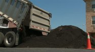 Truck dumps soil onto street Stock Footage