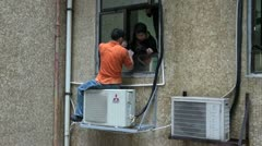 Workers are busy fixing an airconditioner in Hong Kong Stock Footage